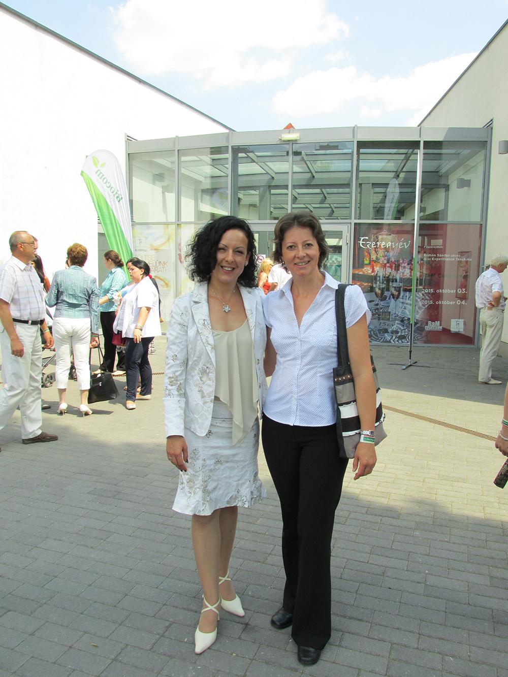 Két vezető mosolyog a kamerába. Ujvári Zsuzsi és Gőz Ildikó egy budapesti, nemzetközi rendezvényen.