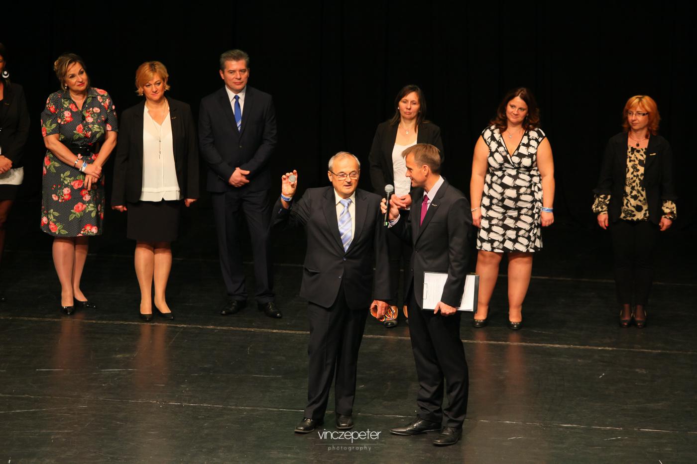 A népszerű, és ezúttal is állva megtapsolt feltaláló, Szabó Sigfrid éppen a Reg-Enorért kapott Géniusz.díjat mutatja. A másik kezében pedig egy nemzetközi kiállításon kapott bronzérem - ugyanezért.