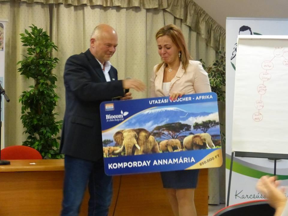 A meglepetés pillanata: Kónya György hálózatigazgató adja át szimbolikusan Komporday Annamáriának az afrikai utazásra invitáló vouchert