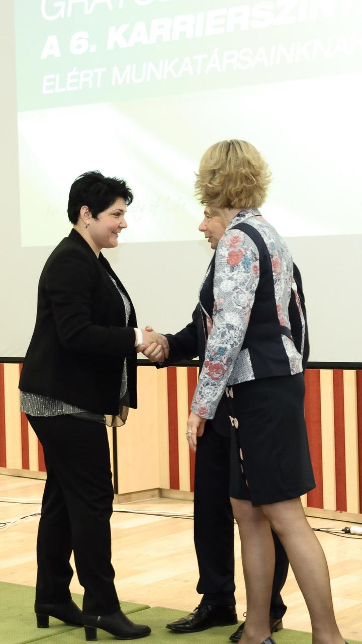 Itt még a hatos karrierszinthez (Társult Hálózatvezető) gratulál neki egy nagyrendezvényen Ferenczy László hálózatigazgató és Borbáth Edit, a romániai partnercég ügyvezetője