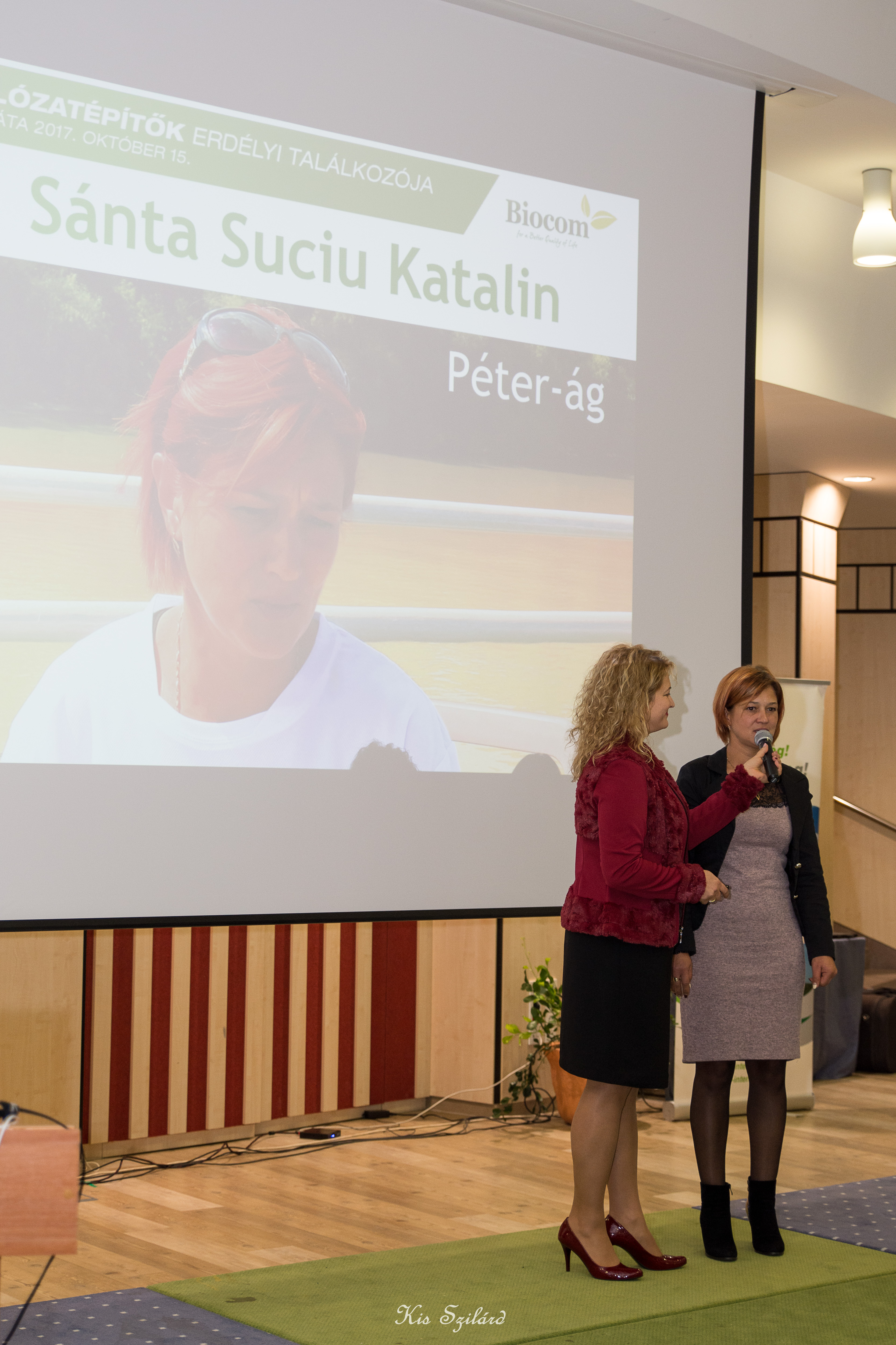 """Vass Szombatfalvi Zsuzsa előadása nagy részében mások elé tartotta mikrofonját. Volt oka rá: a Vass-ág adta a legtöbb nyári, """"hajózós"""" versenygyőztest az egész Biocomban! Itt éppen Sántha Suciu Katalin """"nyilatkozik"""" neki és a közönségnek."""